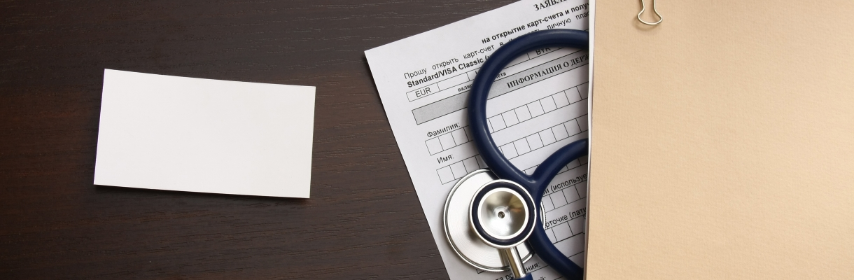 A blank, a medical record form with a  stethoscope on a wooden desk